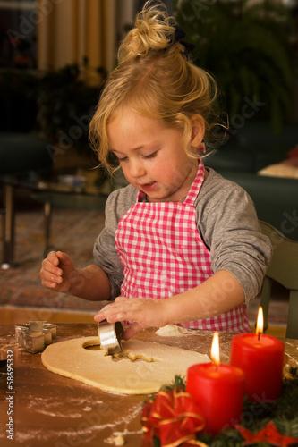 Kind zu Weihnachten im Advent beim Plätzchen backe