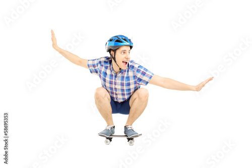 Young smiling male with helmet skating on a skate board