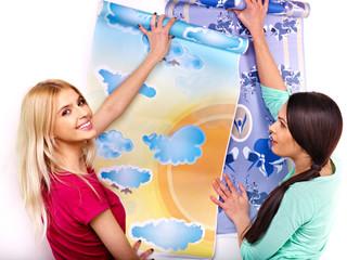 Women glues wallpaper at home.