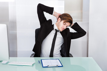 Young Businessman Stretching At Office Desk
