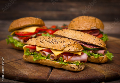 Sandwiches on the wooden table - 58704170