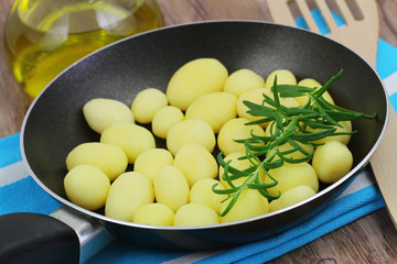Baby potatoes with fresh rosemary in frying pan