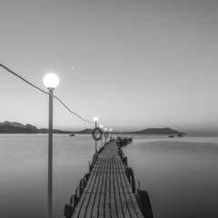 Jetty on sea at dawn. Black and white.