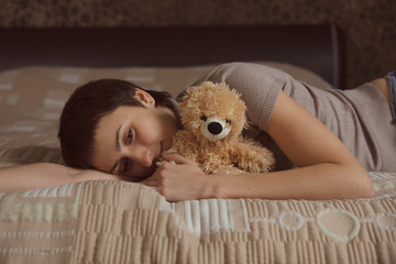 Young woman lying on the bed with a teddy bear