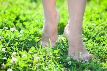 Front close-up view of female legs stepping on green grass