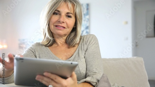 Senior woman in sofa websurfing on internet