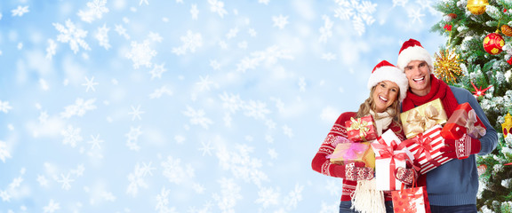 Happy christmas couple over snowy background.