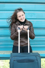 Pretty young curly redhead woman with suitcase a metal wall at t