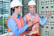 Asian technicians at panel on construction site