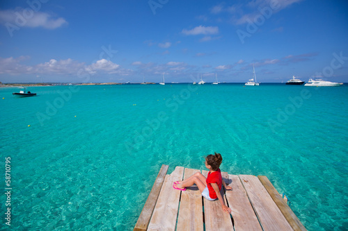 Kid girl looking at tropical Mediterranean sea from wood pier