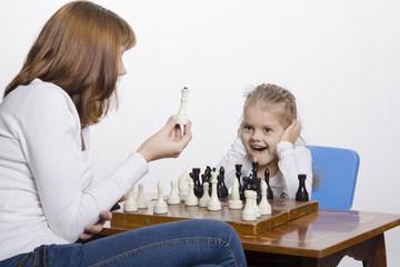 Мама объясняет дочке назначение шахматных фотографии