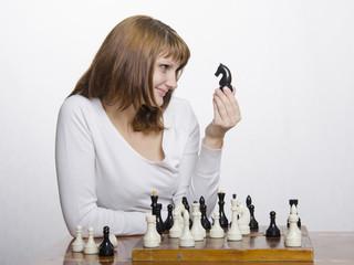 девушка весело смотрит на фигуру коня, играя в шахматы