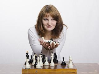 девушка держит горсть шахматных фигур
