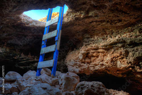 Cave hole entrance with ladder in Barbaria Cape