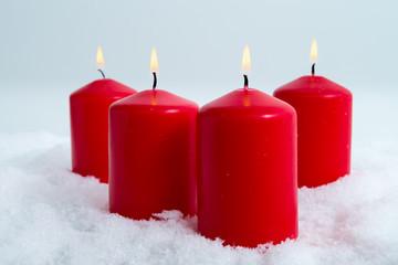 Vier Kerzen im Schnee