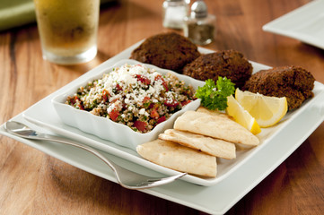 Dinner plate with falafel, tabbouleh and pita bread.