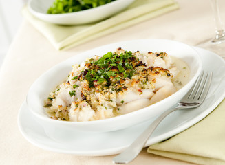 Closeup of a scallop gratin sprinkled with parsley.