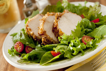 salad with slices of pecan-crusted chicken