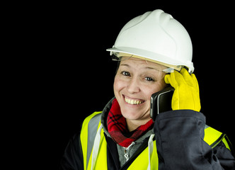 female builder happy on phone wearing vest and safety helmet
