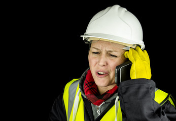 female builder unhappy on phone wearing vest and safety helmet