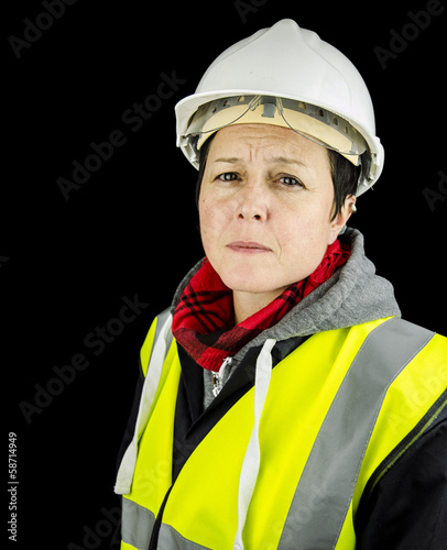 female builder unhappy wearing vest and safety helmet