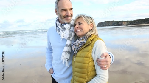 Cheerful senior couple walking on the beach