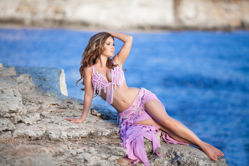 Beautiful woman bellydancer in purple costume