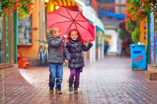 happy kids walking under the rain on colorful street