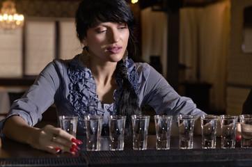 Woman drinking heavily at a bar