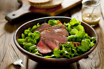 green salad with sliced seared tenderloin steak.