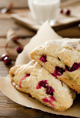 cranberry scones with a glass of milk in a fall setting.