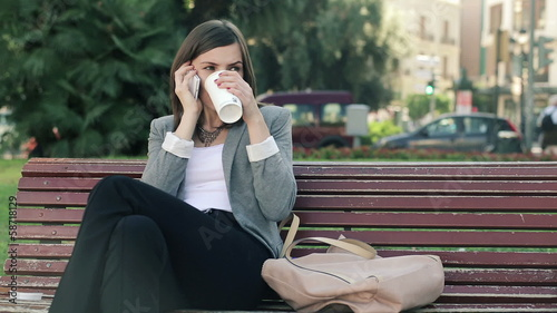 Businesswoman drinking coffee and talking on cellphone in  city