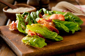 Charred romaine lettuce and crispy bacon on skewers