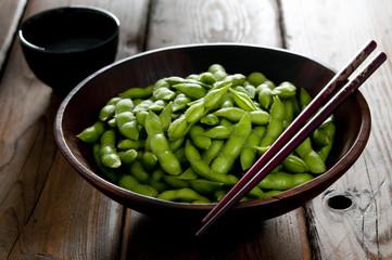 Closeup of salted edamame with chopsticks and tea.