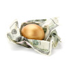 A goled egg on a pile of dollars.