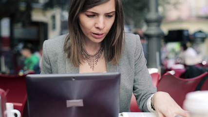Young Businesswoman working with laptop and newspaper in cafe