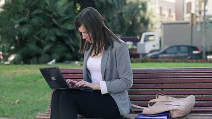 Young businesswoman working on laptop in the city