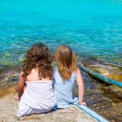 Blond and brunette kid girls sitting on beach port