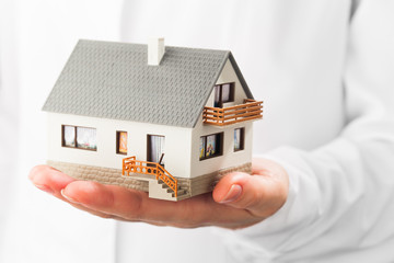 miniature house on hand, white background