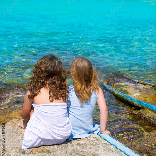 Blond and brunette kid girls sitting on beach port