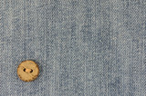 Denim background with old wooden button