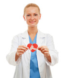 A female doctor holding a wounded paper heart