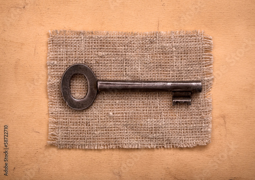 Old key on sackcloth