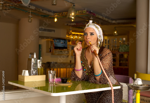 Arabian lady smoking hookah in the coffee shop
