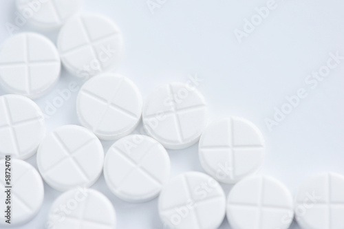 White pills on a white background