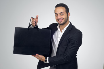 Handsome young man holding a black shopping bag