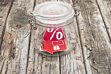 sign percent in a glass jar on wooden table