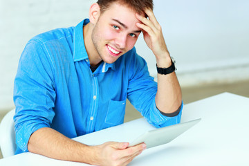 Portrait of a young businessman holding tablet computer