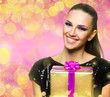 Beautiful woman holding a  gift over a colorful shiny background