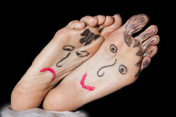 Painted faces on the woman's feet